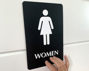 Womens restroom sign with braille