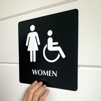 Braille women's room sign with ADA symbol